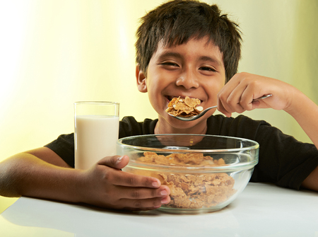 healthy snack: happy boy at breakfast isolated on yellow background Stock Photo