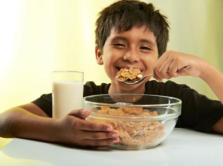 comiendo cereal: niño feliz en el desayuno aislado en fondo amarillo