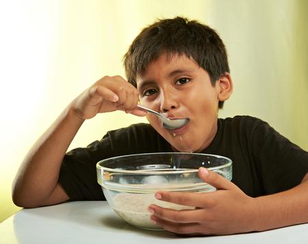 comiendo cereal: ni�o con la cuchara en la boca que come el cereal