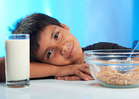 cute latino boy on breakfast with cereal and milk 스톡 콘텐츠