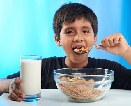 comiendo cereal: latino boy eating cereal isolated on blue background Foto de archivo