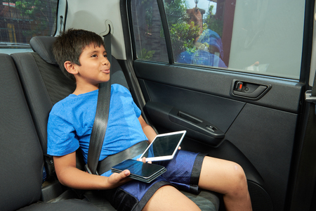 ist: cute boy with tablet and phone ist in car Stock Photo