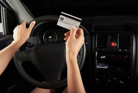 Bestuurder houden creditcard binnenkant van auto dashboard