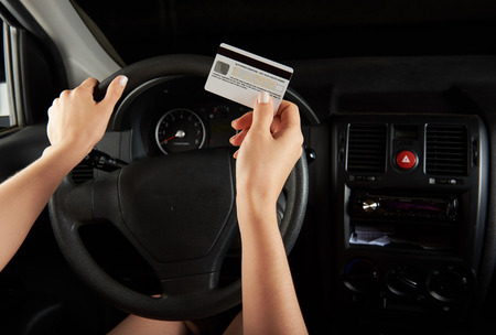 driver hold credit card infront of car dashboard