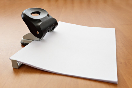 paper puncher: black hole puncher with paper on wood office table