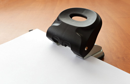 hole puncher: Hole puncher with paper on wood office table