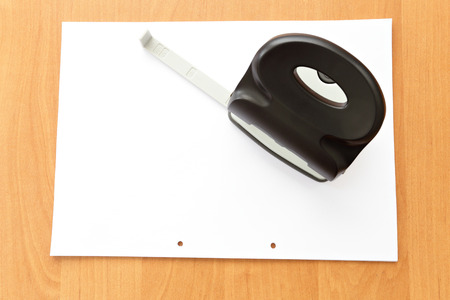 paper puncher: Hole puncher with paper on wood office table and paper with holes