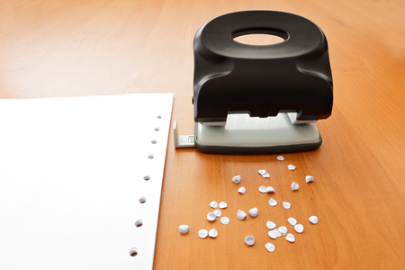 paper puncher: Hole puncher with paper and confetti on office table