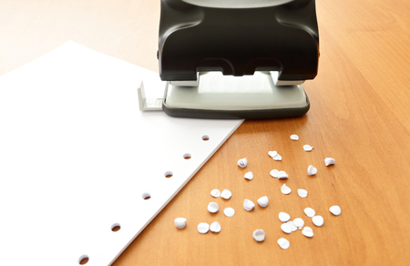 paper puncher: Hole puncher with paper and confetti on wood office table