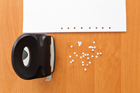 paper puncher: Hole puncher with paper and confetti on the office table