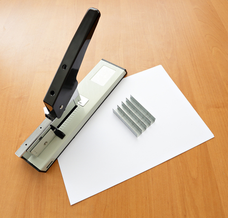 metal fastener: Stapler and staples with paper lay on wood table