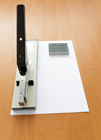 metal fastener: Stapler and staples with paper on wood table Stock Photo