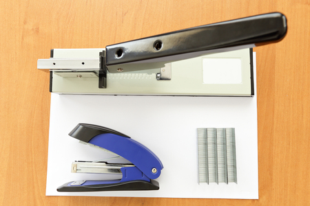 metal fastener: Big and small staplers with staples and paper on wood table