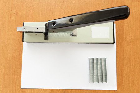 metal fastener: big stapler and staples with paper on the table Stock Photo
