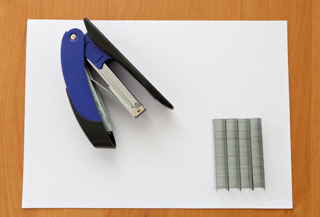 metal fastener: Blue stapler and staples with paper on wood table