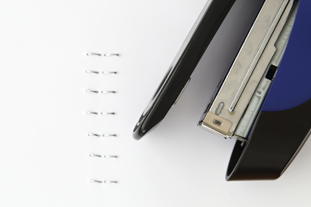 metal fastener: Blue stapler and staples with paper on white table