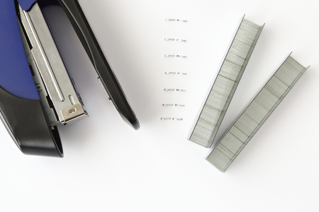 metal fastener: Blue stapler with staples and paper on white table