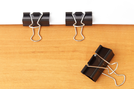 Two clips stapling papers on wood table background