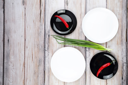 scallions: Red hot chilli pepper and scallions on black plate wooden background