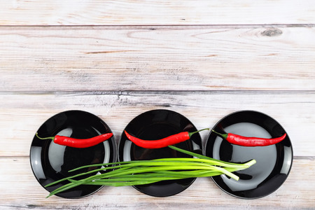 scallions: Red hot chilli pepper and scallions on black plate