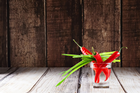 scallions: Red hot chilli peppers and scallions in glass of water on wooden background