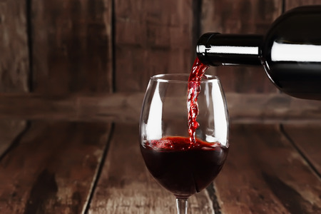 Red wine is poured to glass on wooden background Stock Photo
