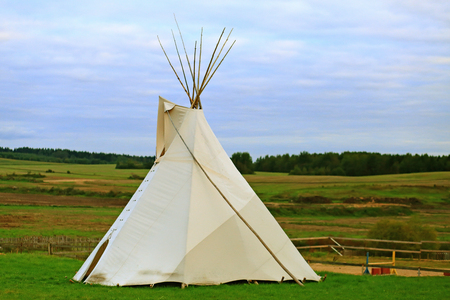 White wigwam on green field in the evening