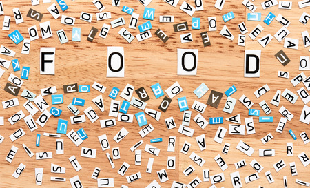 single word: Food word from cut out letters on wooden table Stock Photo