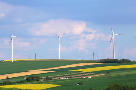 green power: Wind power turbines on sunny day on green field Stock Photo