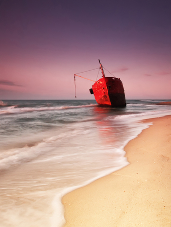 red ship after wreck on the coast with smooth water