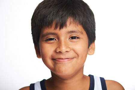 portarit: portrait of hispanic little boy with smile isolated on white