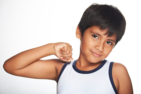 showing muscles: hispanic boy showing muscles isolated onwhite background Stock Photo