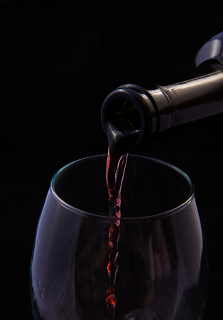 Red vine pouring from bottle into a glass
