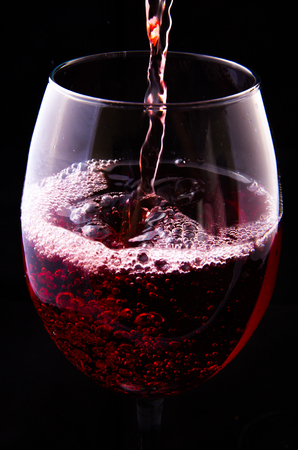 Red vine pouring into a glass on black background