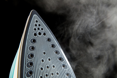 electric material: Iron blowing off steam isolated on black background
