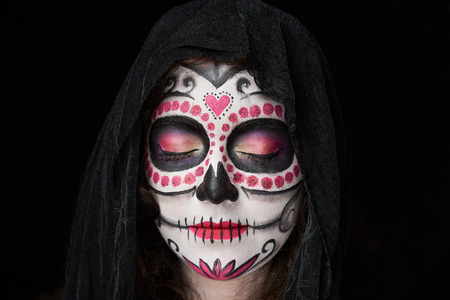 close up of skull halloween makeup on woman isolated black