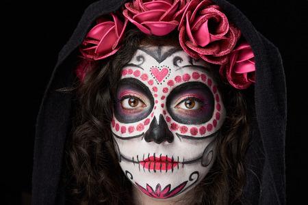 Kopfschuss von catrina Schädel mit roten Rosen und Mantel isoliert auf schwarz