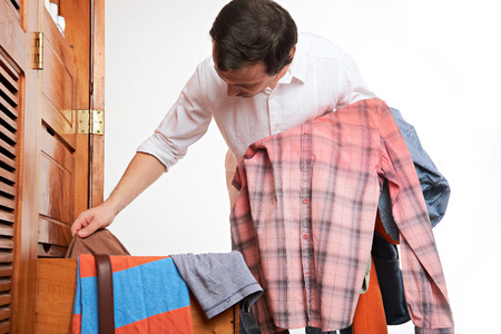 young man choosing cloth in wardrobe isolated on white Stock Photo