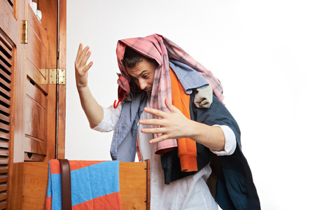 man with his wardrobe looking for clothing Imagens