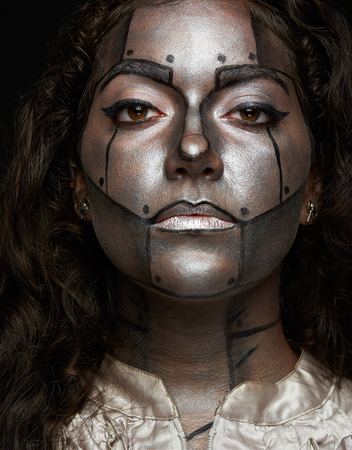 painted face: women serious look with body art painted face of metal robot Stock Photo