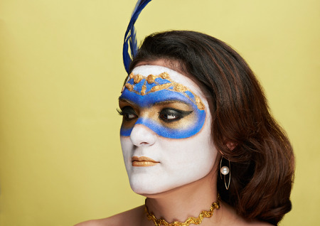 bodypainting: women look on side with painted mask on yellow background