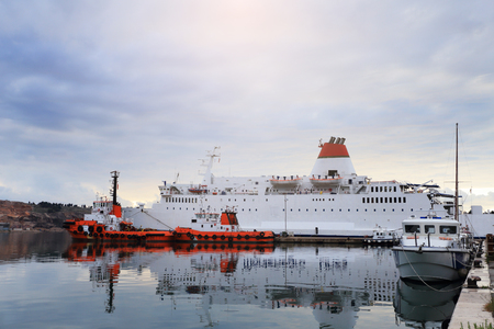 docked: White ferryboat and red tugboats in port in the evening Stock Photo