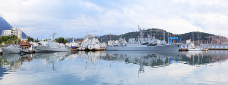 docked: Gray warships docked in  port on a cloudy day Stock Photo
