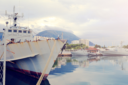 Gray old warships in  port in the evening Фото со стока