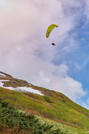 man fly in green paraplane in sunny day Stock Photo