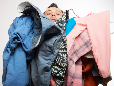 Man covered of stack dirty clothes. One men holding a lot of dresses isolated on white Stock Photo