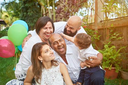 Familia latina diviértete en el jardín con un hijo pequeño