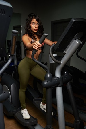 sexy latina: Young woman in elliptical machine at gym. Sexy latina girl walking