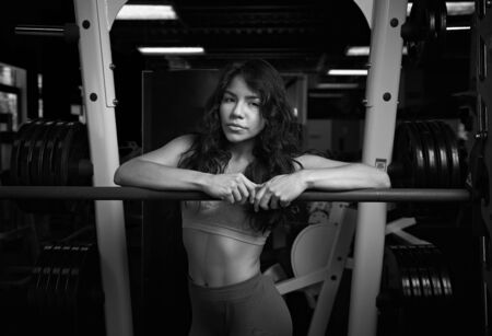 sexy latina: Power lifting latina girl in gym after workout. Sexy hispanic sporty girl black and white colour Stock Photo