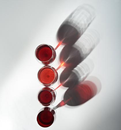 赤ワインと 4 つのワイングラスが白いテーブルの上に立つ